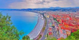 Vista Niza de la ciudad, playa en la puesta del sol, Promenade des Anglais, ` Azur, riviera francesa, mar Mediterráneo, Francia d fotografía de archivo