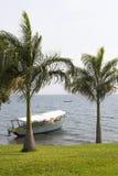 Vista no barco amarrado perto do litoral verde com palmas imagem de stock