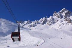 Vista no cabine em declive alpino da inclinação e do elevador Fotografia de Stock