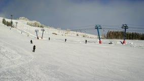 Vista no elevador de esqui longo no monte para esquiar Os esquiadores ascensão a montanha e alguns têm chegado já para baixo de video estoque