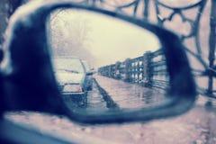 A vista no espelho de rearview lateral do carro no wea inclemente Imagens de Stock