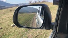 a vista no espelho lateral, o carro move fora de estrada no Cáucaso, movimento lento vídeos de arquivo