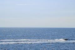 Vista no horizonte e mar aberto com o barco da velocidade que passa perto Fotos de Stock Royalty Free