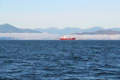 A vista no navio de carga igualmente chamou o cargueiro nas águas da baía na península de Kamchatka, Rússia de Avacha fotografia de stock