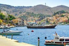 A vista no porto grego do porto da ilha de Symi do mar, navio clássico yachts, casas em montes da ilha, baía do Mar Egeu dos turi Fotografia de Stock