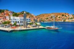 A vista no porto grego do porto da ilha de Simy do mar, navio clássico yachts, casas em montes da ilha, baía do Mar Egeu dos turi imagem de stock royalty free