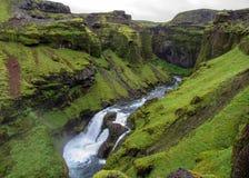 Vista no rio de Skoga com a cachoeira no dia de verão chuvoso na fuga de Fimmvorduhals de Skogar a Thorsmork, montanhas de Islând imagem de stock