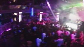 Vista no salão do tolo do clube noturno de povos da dança fontes iluminações DJ que executa na fase filme
