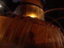 Vista nocturna de la agua corriente del parque de Herzel de la fuente local de la rana, iluminada por las luces ámbar calientes foto de archivo libre de regalías
