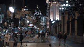 Vista nocturna de la calle animada de Alcala con la entrada de la estación de metro, Madrid metrajes