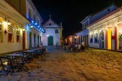 Vista nocturna de la calle del centro histórico con las tablas de restaurante en Paraty, Rio de Janeiro, el Brasil fotografía de archivo libre de regalías