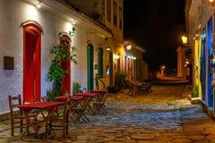 Vista nocturna de la calle del centro histórico con las tablas de restaurante en Paraty, Rio de Janeiro, el Brasil fotografía de archivo