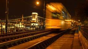 Vista nocturna de la tranvía de la ciudad en el fondo del puente de cadena en Budapest, Hungría Foco selectivo El viajar a Hungrí fotografía de archivo