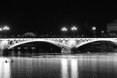 Vista nocturna de Sevilla con su río Guadalquivir y Torre del Oro fotos de archivo