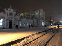 Vista nocturna del ferrocarril en la ciudad de Cherepovets, Rusia La gente cruza los carriles teniendo en cuenta las linternas foto de archivo libre de regalías