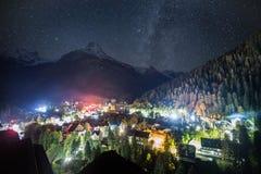 Vista nocturna del pueblo de Dombay contra la perspectiva del cielo nocturno fotografía de archivo
