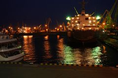 Vista nocturna del remolcador en el puerto del cargo de Odessa Los tirones y una grúa flotante están en puerto Panorama de la noc fotos de archivo