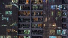 Vista nocturna del timelapse exterior de la construcción de viviendas Alto rascacielos de la subida con las luces del centelleo e almacen de metraje de vídeo
