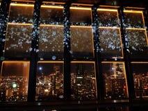 Vista nocturna que sorprende de la torre al ver a través la ventana imagenes de archivo