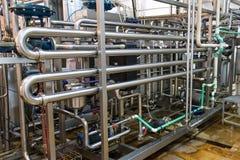 Vista nos encanamentos do aço na fábrica do leite imagens de stock royalty free