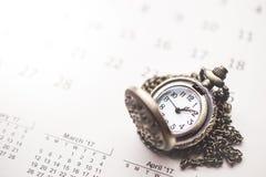 Vista nostalgica con l'orologio da tasca d'annata sul calendario e sulla stazione termale Immagini Stock