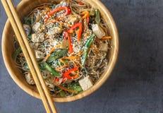 Vista op di un piatto di legno orientale con il piatto del vegano delle tagliatelle di vetro immagine stock