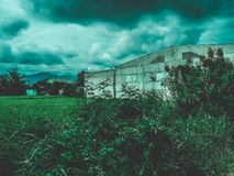 Vista original de uma construção velha no fieild com mountians Imagens de Stock Royalty Free