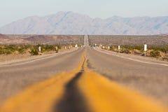 Vista orizzontale classica di panorama di una strada diritta senza fine che passa il paesaggio sterile dell'americano fotografia stock