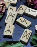 Vista orizzontale delle rune di legno che si trovano su un fondo di pietra scuro fotografia stock