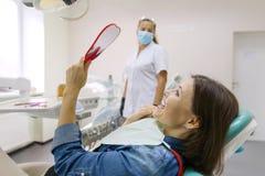Vista paciente da mulher no espelho nos dentes, sentando-se na cadeira dental foto de stock royalty free