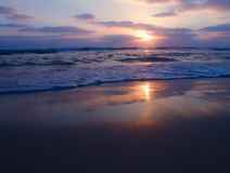 Vista pacifica di un tramonto nuvoloso sulla spiaggia sabbiosa con le belle riflessioni sulla sabbia bagnata immagine stock libera da diritti