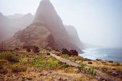 Vista panorámica al pico de montaña de Aranhas en el valle con las ruinas de la casa y la trayectoria que camina pedregosa que va imagen de archivo
