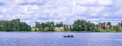 Vista panorámica de la iglesia ortodoxa en la orilla del lago que camina por el agua Fotografía de archivo