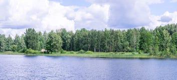 Vista panorámica de la iglesia ortodoxa en la orilla del lago que camina por el agua Foto de archivo