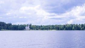 Vista panorámica de la iglesia ortodoxa en la orilla del lago que camina por el agua Imagenes de archivo