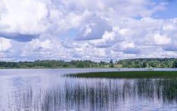 Vista panorámica de la iglesia ortodoxa en la orilla del lago que camina por el agua Imagen de archivo libre de regalías