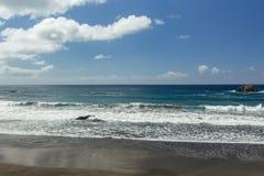 Vista panorámica de la playa de Aimasiga con la arena negra volcánica y las rocas solitarias que se pegan fuera de la espuma del  imagen de archivo
