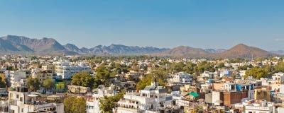 Vista panorámica de los edificios rodeados por los árboles verdes contra el cielo azul en Udaipur Fotos de archivo libres de regalías