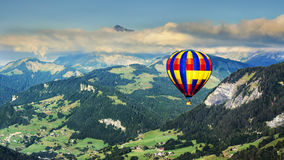 Vista panorámica de montañas con un globo del aire caliente Foto de archivo libre de regalías