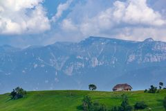 Vista panorámica de un paisaje de la primavera en las montañas, con una casa del sheepfold en los picos, los árboles dispersados  imagenes de archivo