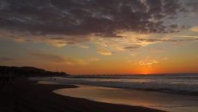 Vista panorámica de una puesta del sol nublada en la playa mientras que el sol está ocultando en el horizonte almacen de video