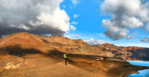 Vista panorámica del paisaje geotérmico hermoso con la mujer que se coloca en la montaña superior cerca del lago del cráter de Ask Imagenes de archivo