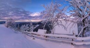 Vista panorámica del paisaje hermoso de la montaña en tonos rosados con una casa nevada, árboles y una cerca de madera At Sunrise foto de archivo libre de regalías