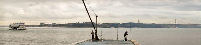 Vista panorámica del río Tagus en Lisboa con el transbordador, los pescadores, la estatua y 25 de Abril Bridge de Cristo Rei Imágenes de archivo libres de regalías