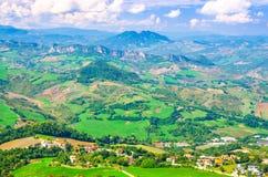 Vista panorámica superior aérea del paisaje con el valle, las colinas verdes, los campos y los pueblos de la república San Marino foto de archivo