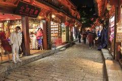 Vista panorámica a una de las calles en la ciudad vieja de Lijiang en la puesta del sol con algunos turistas que pasan cerca Fotografía de archivo libre de regalías