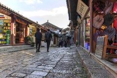 Vista panorámica a una de las calles en la ciudad vieja de Lijiang en la puesta del sol con algunos turistas que pasan cerca Imágenes de archivo libres de regalías