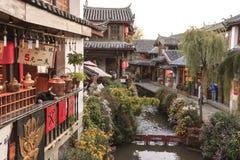 Vista panorámica a uno de los canales en la ciudad vieja de Lijiang en la puesta del sol con algunos turistas que pasan cerca Fotografía de archivo libre de regalías