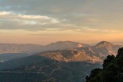 Vista panorâmica da paisagem da montanha no por do sol O último sol irradia-se nas partes superiores das montanhas perto do monas Imagens de Stock