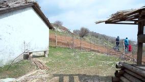 Vista panorâmica da vila Barco de madeira preto dilapidado velho com uma casa do um-andar, um poço e um monte De madeira velho filme